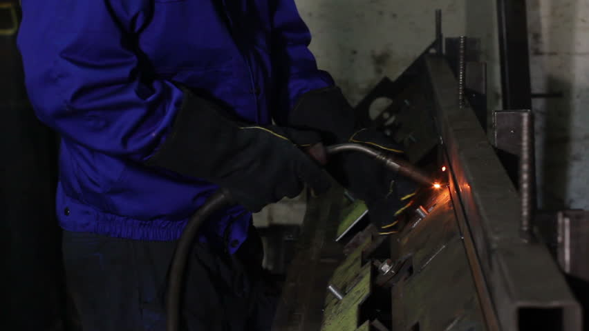 Welder with torch is welding metal on construction site
