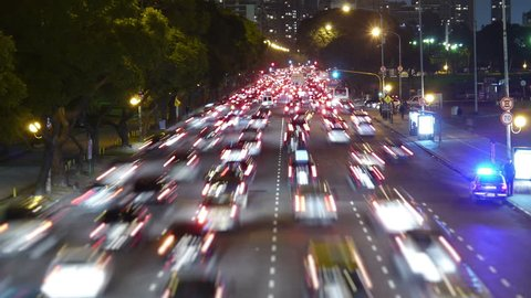 Traffic in the city. Avenue Time-Lapse, Night. Moon going down. Heavy traffic / jam / flowing with blurred motion. Dusk. Dolly out / zoom.