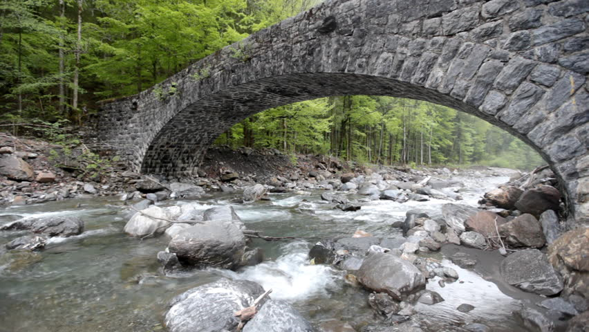 Montain river with an ancient stone bridge in Swiss Alps