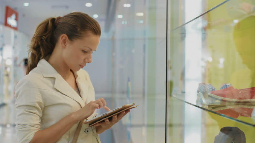 Beautiful business woman standing near shop window and makes notes in the tablet | Shutterstock HD Video #4092694