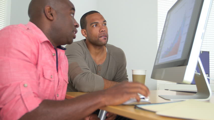 Two Black Business men looking at sales data