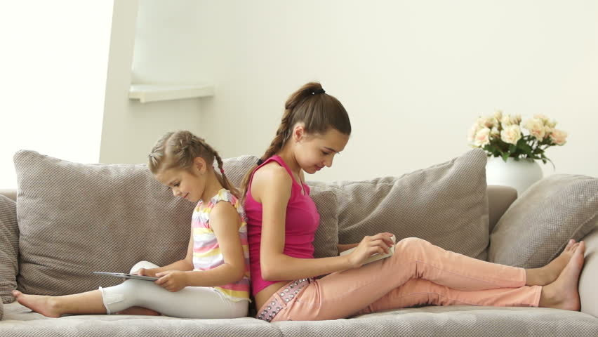 Two sisters sitting on the couch with a book and a tablet. They are smiling