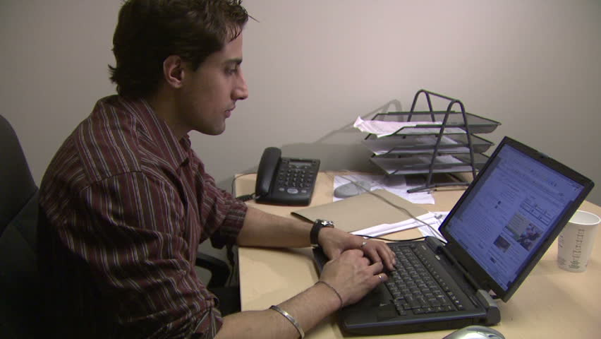 Employee researching Internet in his office. Perfect shot as a B-roll for a story on business/ work related issues or on Internet addiction.