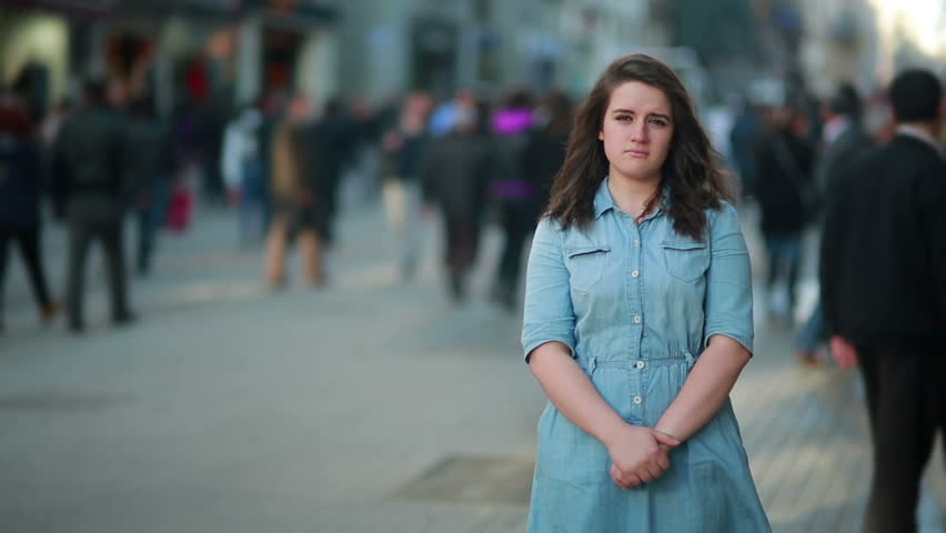 Portrait of sad young woman standing in busy city street
