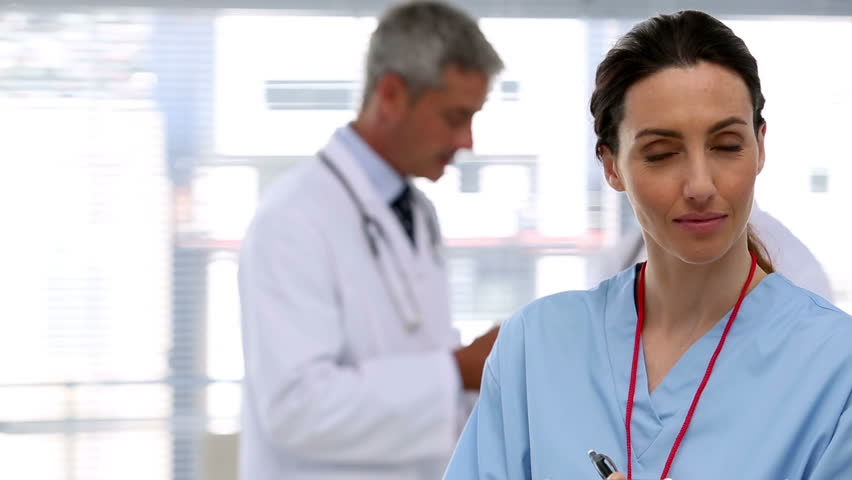 Smiling nurse holding clipboard and her coworkers on the background