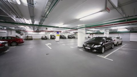 Many cars stand in underground parking with piping and illumination