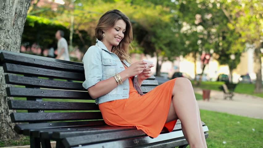 Pretty happy woman using smartphone in city park, steadicam shot