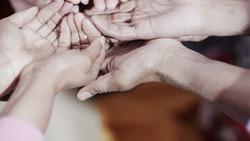 The many hands of adults and children from a poor community are reaching out for help, begging for food or money.