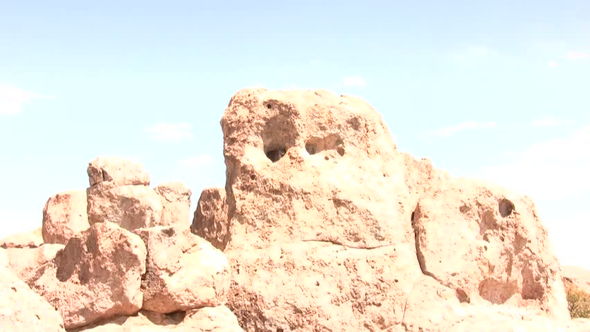 HD clip of a wide view of a rock formation, zooming into one of the holes, where a Great Horned Owl is sleeping quietly just out of the breeze
