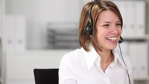 Young smiling businesswoman talking on headset in the office