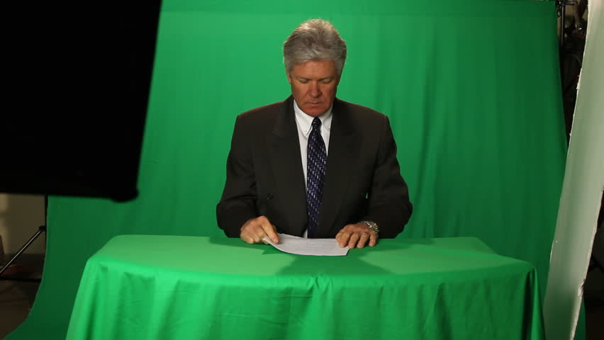 NEWSMAN/ANCHORMAN AGAINST GREEN SCREEN.A newsman or anchorman or spokesperson against green screen.