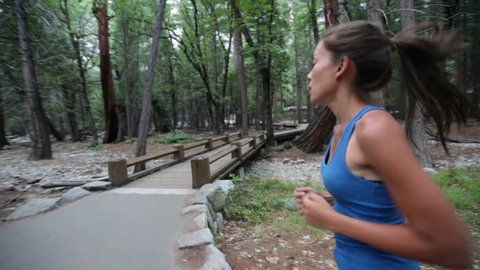 Running - woman runner jogging on forest path in Yosemite National park. Fit Asian female sport fitness model athlete trail running training for cross country race.