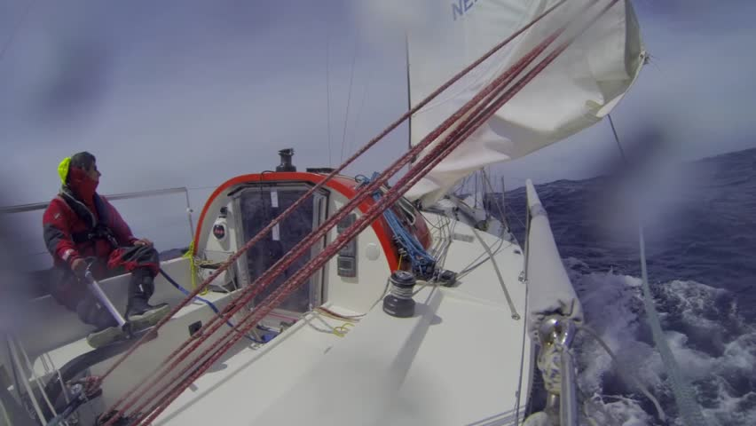 Single handed sailor steering his small yacht at hight speed,  during a race over the Atlantic Ocean