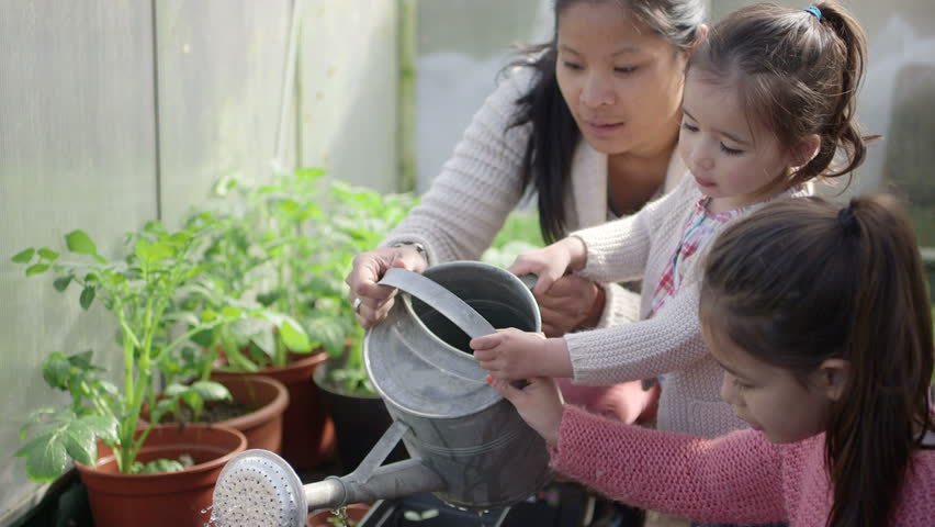 Mother teaching daughters in greenhouse