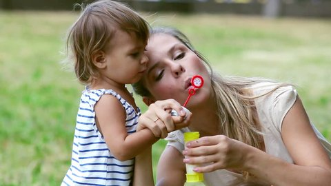 Mother entertaining her baby girl by making iridescent soap bubbles