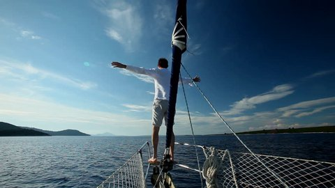 Man standing on the bow of sailing boat on Mediterranean sea.