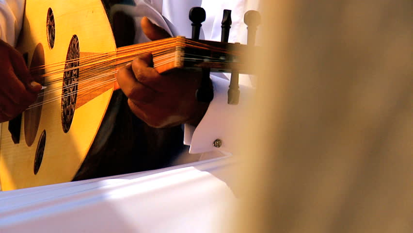 Close up middle eastern male hands playing traditional Arabic Oud or guitar