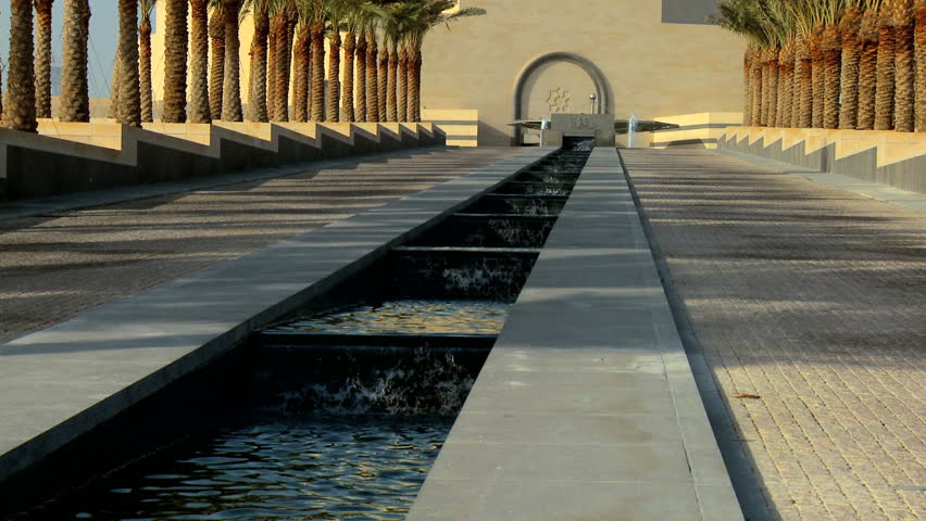 Clear running water in avenue of palm trees in front of Islamic Museum of Art, Doha, Qatar