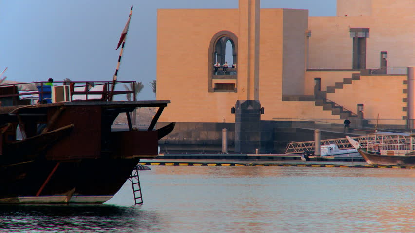 Traditional sailing dhows in the harbor of Doha, Qatar Islamic Museum of Art background
