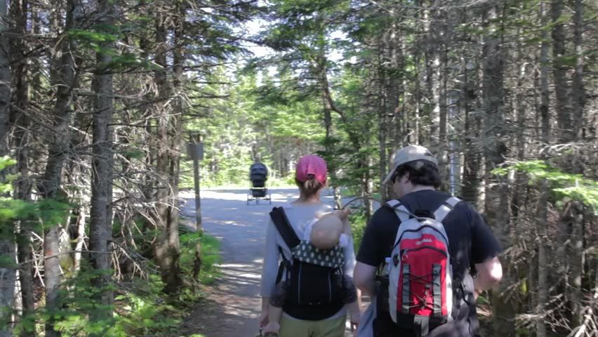 A young family with a baby hiking the skyline trail in Cape Breton, Nova Scotia