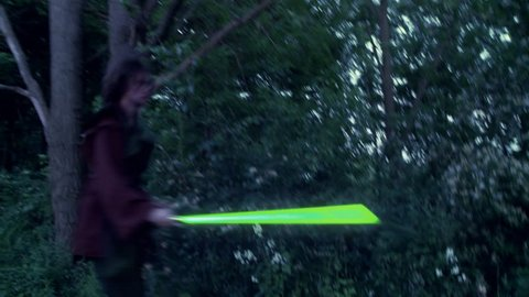 Two men duel with futuristic glowing green laser swords.  Fighting on grassland in front of woods.  Hand held camera.  Long shutter speed creates large light trails from the lasers.