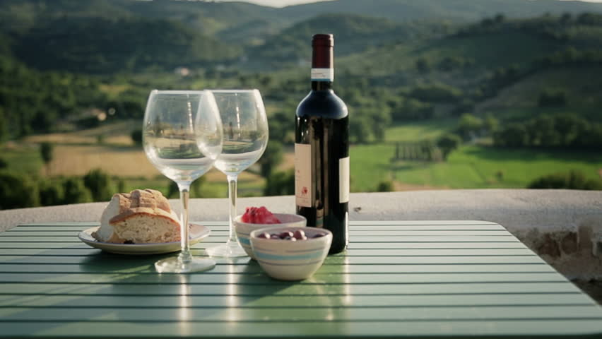 Table with wine and appetizer on italian landscape