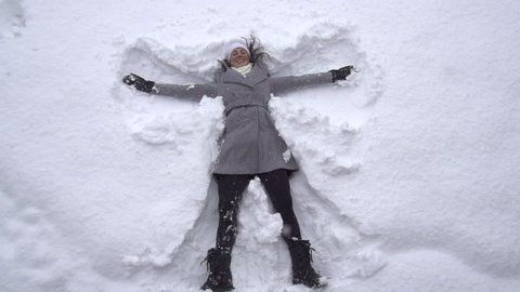 SLOW MOTION: Young woman making snow angels