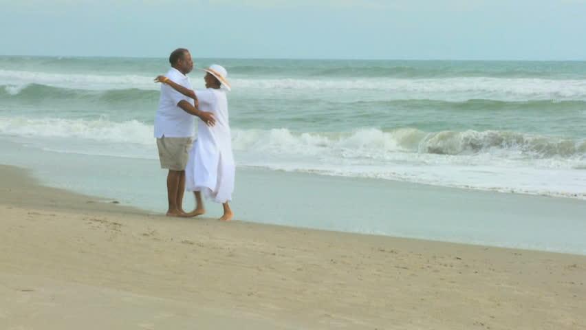 Senior ethnic couple having fun dancing together on beach head shoulders