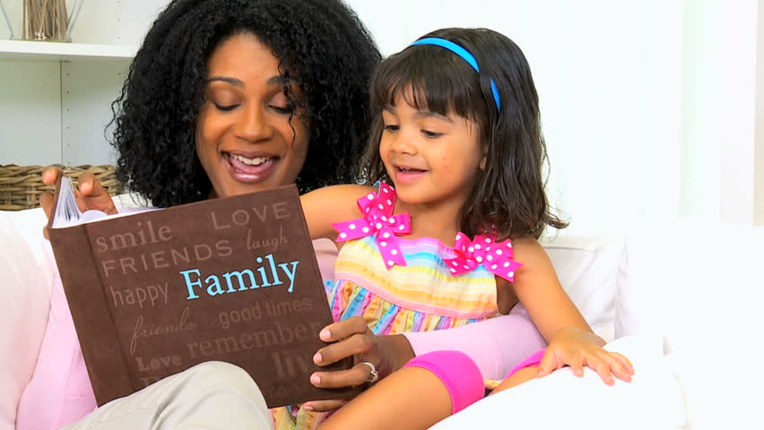 Loving African American mother with cute young daughter looking photo album