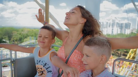 mom with two kids ride on the Ferris wheel. They pretend that fly and look very cheerful and happy