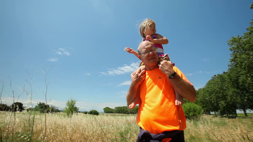 Grandfather carrying grand daughter on shoulders in nature in summer