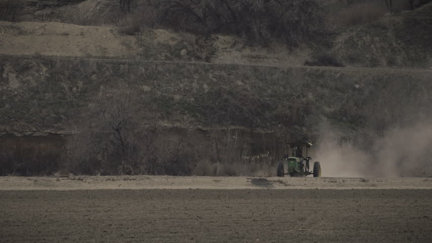 A farmer executes a turn in an old tractor, trailing heavy dust in his wake