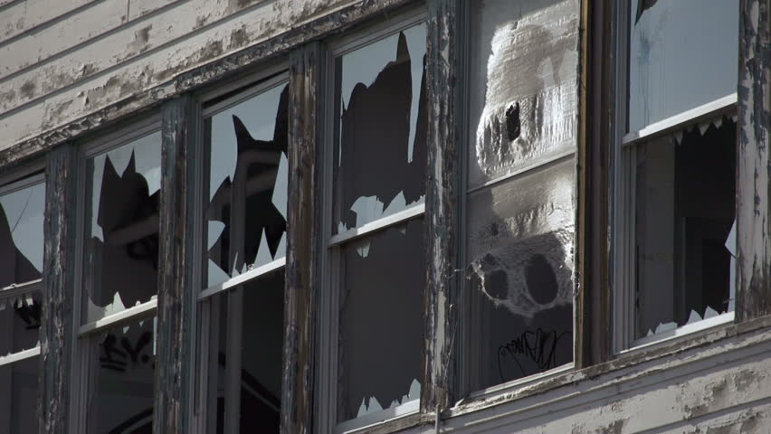 Abandoned building has broken windows ringed with shards of glass and ragged
