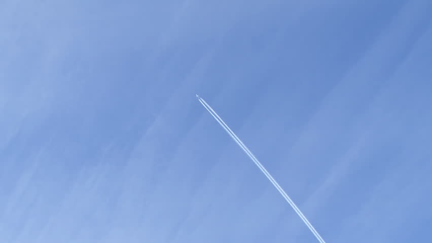 A distant airplane passes high overhead, leaving a jet contrail against a wispy