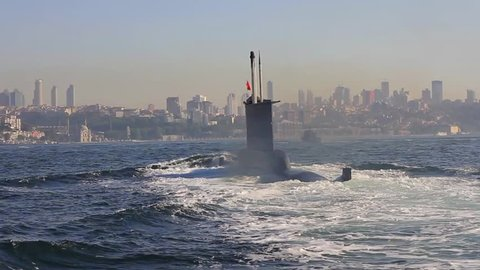 Riding on the wake of the submarine. Navy Submarine moving into Bosporus waters. Tracking shot.