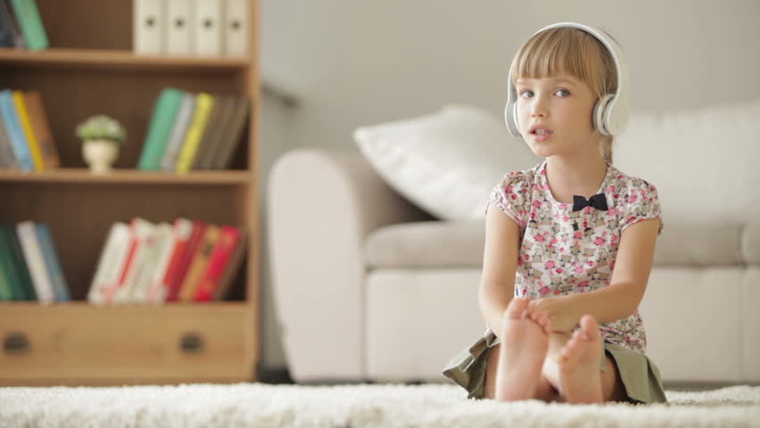 Funny little girl in headphones sitting on carpet in living room singing, moving and clapping her hands to music