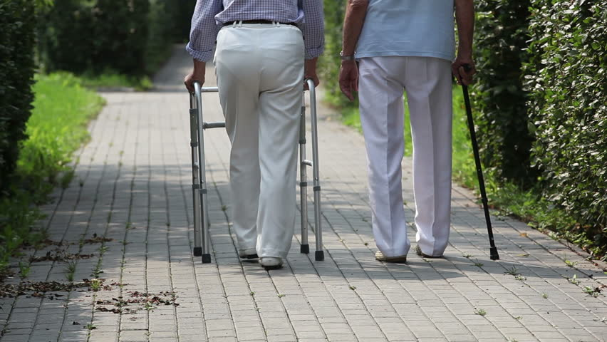 Elderly couple taking steps together with a help of a walker and a cane