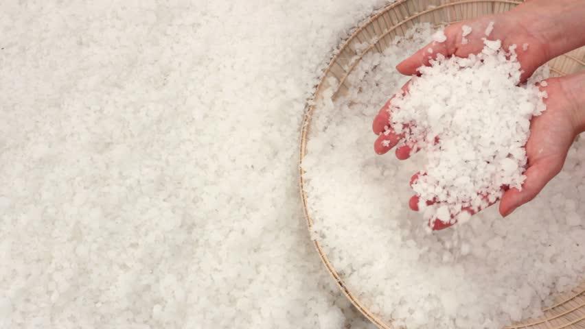 Close-up of huge salt crystals in the hands of a woman. Salt fields of Nha Trang, Vietnam.