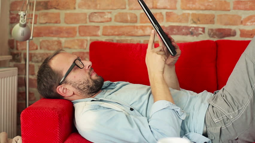 Young man with tablet computer lying on sofa