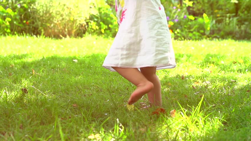 Adorable one year old Baby Girl making her first steps outdoor. Slow Motion Video Footage of the First Steps of the Kid. Sunny day and Green Grass. High speed camera 240 fps