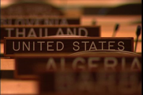 NEW YORK CITY - FEBRUARY 11, 1999: MCU row of wooden name signs for Algeria, United States and Thailand, camera zooms out to show MS of empty seats in  the United Nations General Assembly hall.
