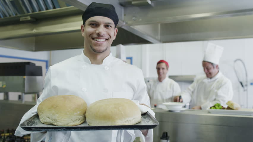 Young male chef in a commercial kitchen holds a tray of freshly baked bread. His colleagues standing in the background smile at his success.