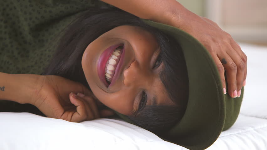 African American girl wearing floppy hat on bed