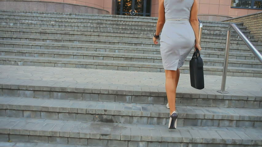 young business woman is sent to the office building for a meeting. She is holding a briefcase. When she climbs the stairs - looks at the clock. She is afraid of being late