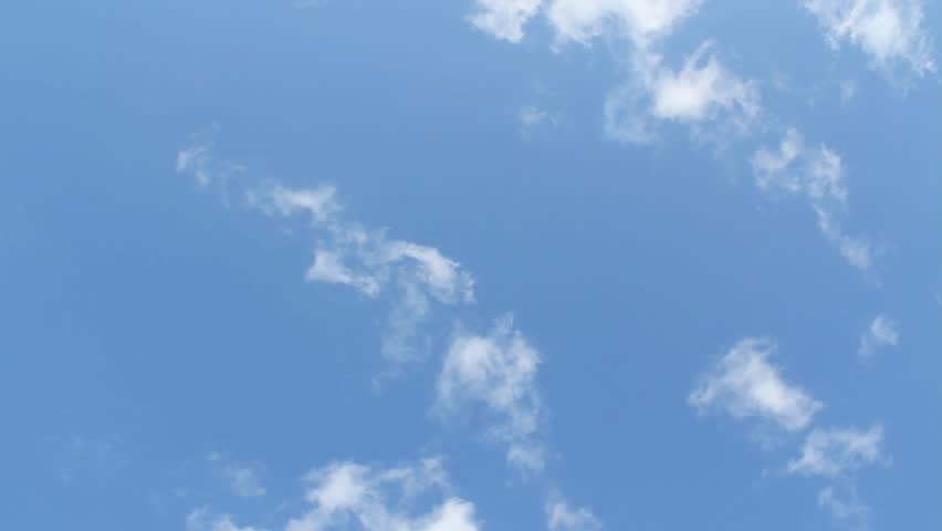 A blue sky with white clouds passing overhead