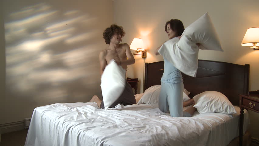 Young Couple Finish Pillow Fighting In Hotel Bedroom Hand Held Camera Stock Footage -4532