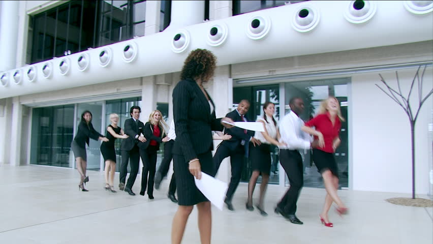 Happy multi ethnic business team dance in a congo line through a large contemporary corporate building. High quality HD video footage