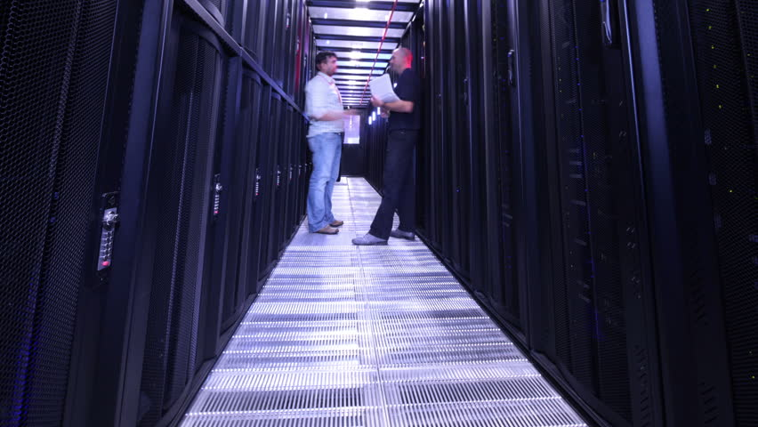 People working in computer server room data center. Walking along rows of super computers, racks and airconditioned cpu's.