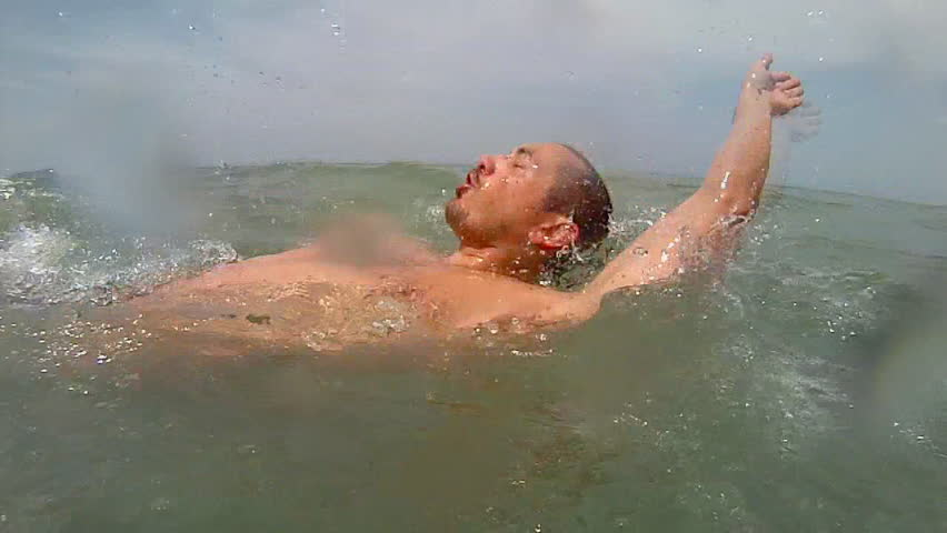 Man does backstroke while open water swimming.