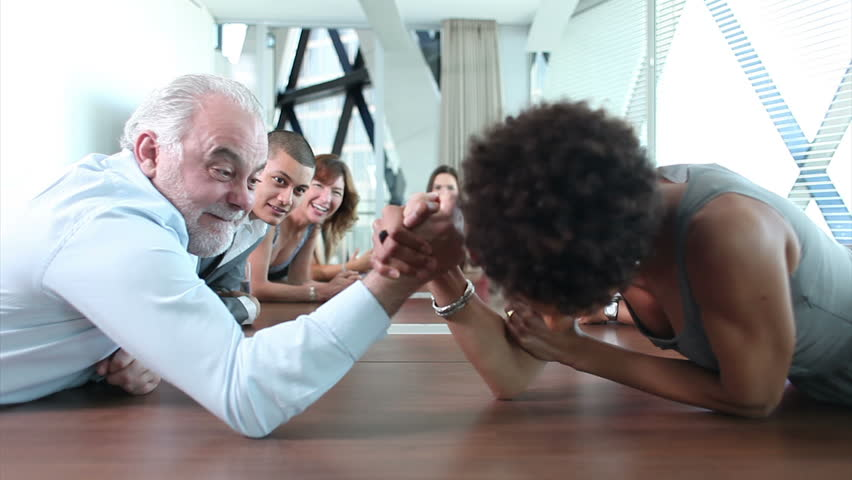 Strange goings on in this funny scene where businessman and woman arm wrestle in large boardroom AGM meeting with mixture of creative looking business people.